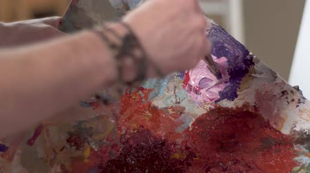 passionate : Man mixing paints on palette, artist aims to get light purple color by combining white and orange paints, closeup Stock Footage