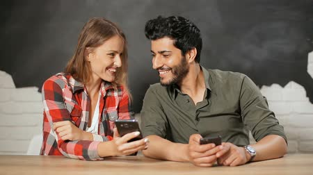 madness : Smiling beautiful woman sharing game result with male friend, showing phone screen to well-built good-looking man using smartphone, concept of life with gadgets all the time