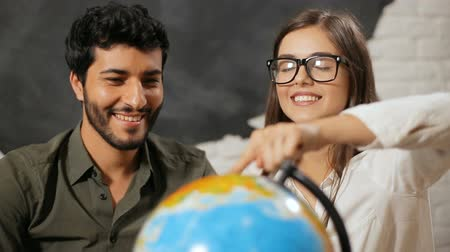 agência : Happy family couple choosing travel destination, thrilled husband turning big globe when dreaming wife with closed eyes points at the country to visit, indoor shot in travel agency