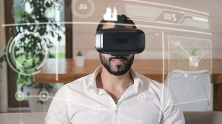 convenção : Handsome bearded arab man uses VR helmet with futuristic visual hologram interface sitting in the kitchen