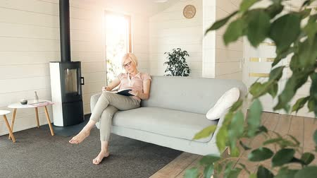 művelt : Intelligent young woman reading an interesting book, spending free time in spacious living room and enjoying the hobby during summer vacation