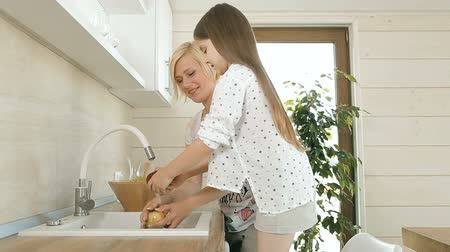 öğrenme : Thrilled mother washing fruits together with excited daughter, concept of spending more time with children