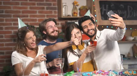 развлекательный : Cheerful friends taking selfie at the birthday party, good-looking young people celebrating important event after work in spacious flat Стоковые видеозаписи