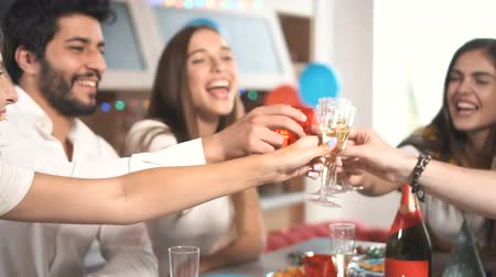 vendég : Happy young people drinking toast during birthday celebration, having great time in relaxing sweet home atmosphere