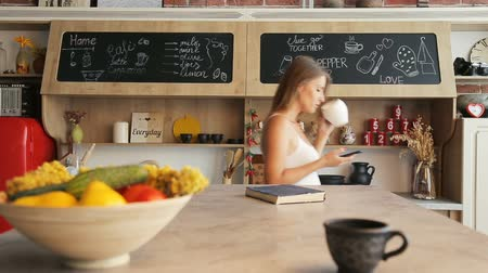 lodówka : Focused slim woman texting message and having morning coffee as walking, indoor shot in modern beautiful kitchen