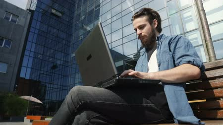 inteligentní : Focused intelligent man using laptop as working outside, wearing casual denim clothes on hectic working day, concept of managing the tasks with technology everywhere Dostupné videozáznamy