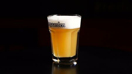 pint glass : Lviv, Ukraine - 24 Sep 2018 Hoegaarden beer in rotating glass cup in slow motion on black background