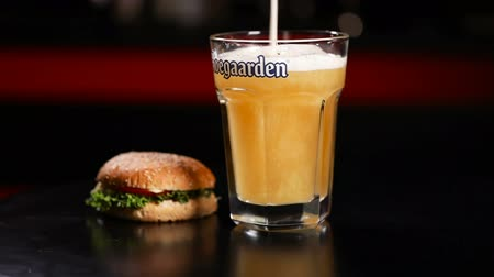 Close up view of burger and cup of beer rotating on black background 影像素材