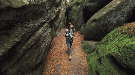 wandering : Excited, slim girl walking in the cave, touching moss-covered, large rocks on the way to experience place never seen before Stock Footage