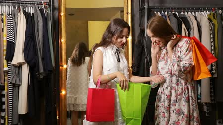 laranja : Excited, pretty woman showing purchase to friend, feeling thrilled indeed after bought great clothes, friends met by chance as going shopping at the weekend