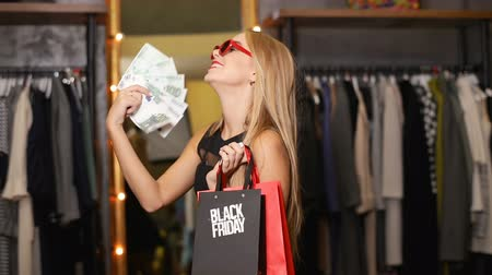 pátek : Joyful female shopper holding lots of money and bags on black friday as buying clothes in expensive designer shop