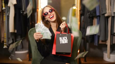 khaki : Rich lady in black sitting cheerfully in comfortable khaki chair in nice clothes shop, holding lots of money on black friday