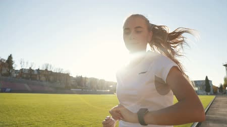hangmagasság : Fair-haired slim woman looking at watch as having morning run, doing workout in the stadium before working day, concept of active lifestyle