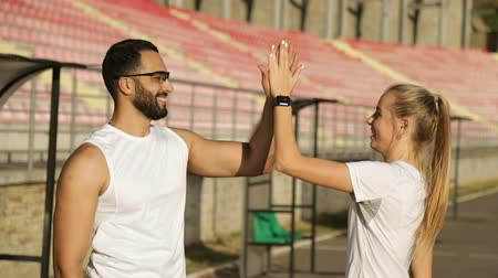 кавказский : Couple of satisfied joggers giving high five to each other, wearing white sportswear during weekend workout on lovely fall day