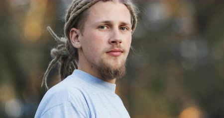 targi : Smiling bearded man with fair dreads standing in park, portrait shoot on peaceful fall morning Wideo