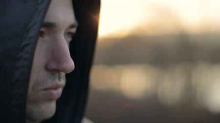 insurgent : Handsome caucasian man is wearing hood, close up view against sunset, november evening time