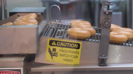 kobliha : Generic doughnut production line (automatic donut machine) with caution sign.
