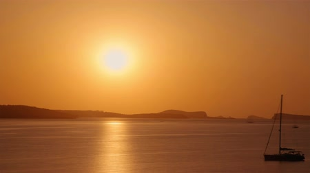 baleár : Sun setting into the sea behind island mountain