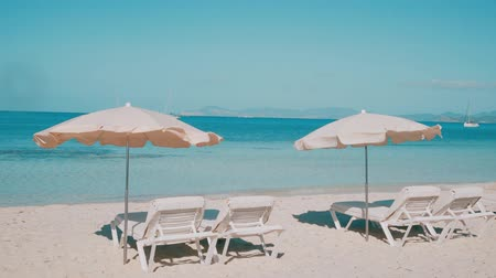 サンベッド : Sun chairs on clean beach overlooking transparent blue sea