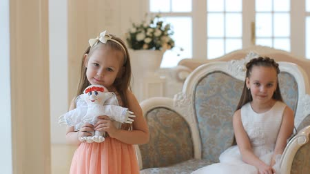 travessura : A girl with a toy angel in her hands. Girls in smart dresses at home on Christmas Day. Two sisters, little girls in a beautiful house. Vídeos