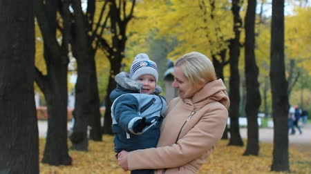 nimet : Young woman with a baby in her arms. Mom and son are resting in a beautiful autumn park.