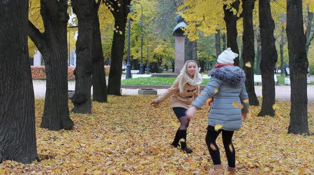 osika : Family holiday in the autumn park. A young woman and her teenage daughter are running around and having fun in the park during the fall of the fall.