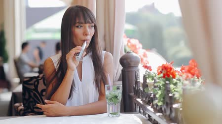 замена : beautiful brunette smoke electronic cigarette on the summer terrace of restaurant
