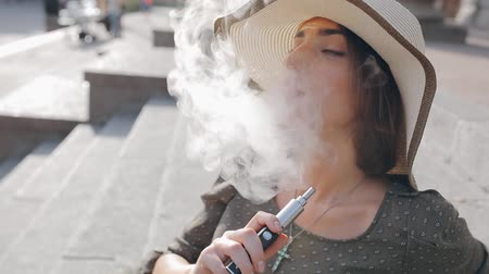 замена : beautiful brunette smoke electronic cigarette in public places