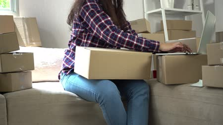 sme : Happy woman Asian young entrepreneur, Checking order in laptop from online shopping store for delivery package to customer from home office, Concept of merchant  business online and eCommerce