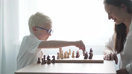 white elephant : a woman is playing chess with a boy wearing glasses. The boy albino in a white rush makes a move