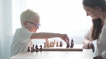 rook : A young albino playing with his mother in chess. They are dressed in white shirts. Move the chess pieces