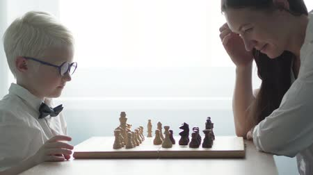 rook : A young albino playing with his mother in chess. They are dressed in white shirts.