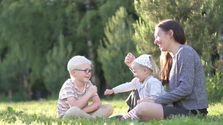 nanny : Mom, son and little daughter are playing with a stone scissors paper in the park. My daughter is sitting with her mother in her arms. Spring is outdoors. The family laughs