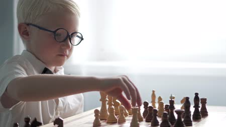 rook : the blond boy is learning to play chess. He sits at the table and thinks over the course. Above him is a white shirt, a butterfly and glasses