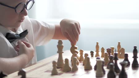 young elephants : A blond boy with glasses is playing chess. Close-up. The course of the horse. Boy moves figures on a chessboard Stock Footage