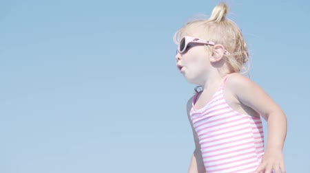 incidence : a little girl stands on the edge of the pool and prepares to jump into the water. On the girl a swimsuit white in pink stripes and pink glasses with dolphins. Slow motion Stock Footage
