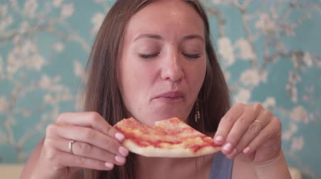 şişman : A girl in a cafe is eating margarita pizza. She holds a piece in her hands, bites pizza and enjoys a meal Stok Video