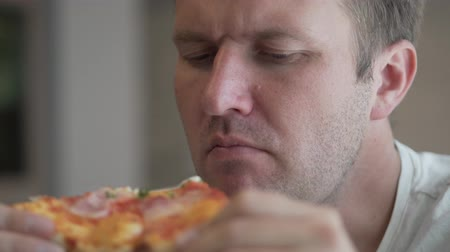 humanóide : the man is eating pizza. On a fat guy, a white T-shirt. He holds a piece of pizza in his hands and eats with an appetite Stock Footage