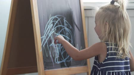 tentar : the little girl draws blue chalk on a blackboard. He takes a rag and starts to erase his drawing. The girl is trying. Classes with kids Stock Footage