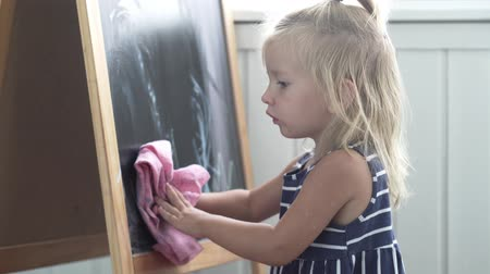 esfregar : The baby erases its picture from the board. The girl is standing at the blackboard and with a pink rag erases the drawn Stock Footage
