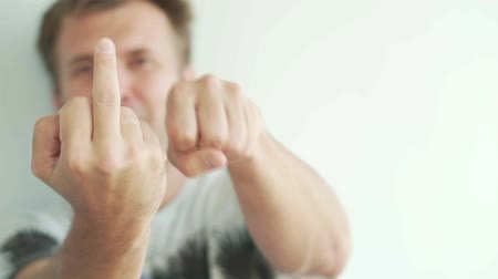 transação : he man shows the middle finger in slow motion. Focus on the fist. The man holds his arm outstretched, the brush is squeezed into the coat and slowly shows Fuck