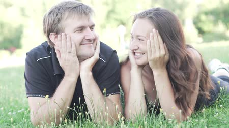 falar : man and woman are lying on the grass after a sports training. They cover their faces with their hands, then they open and smile and laugh. They talk and have fun