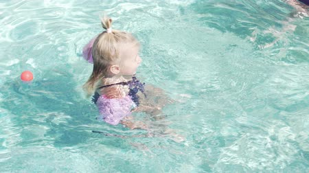 ona : little girl is swimming in the pool. The girls have arm ruffles. She lies on the water and swims. On the girl a swimsuit in polka dots and pink armlets Dostupné videozáznamy