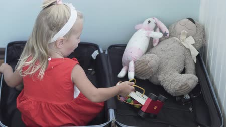 ruha : a little girl is collecting a suitcase on vacation. The girl sits in a suitcase and puts her plush toys into it