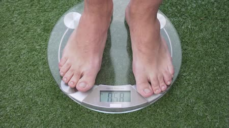 kilogramm : the man stands on the scales to weigh himself. He wants to lose weight. Glass scales lie on an artificial green lawn. The man after training. He has hairy legs