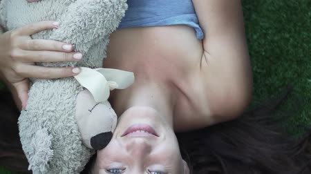 плюшевый мишка : the girl is sleeping on the grass in an embrace with a teddy bear. She wakes up, opens her eyes, smiles. Presses the bear closer to him