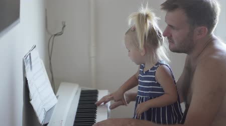 sobre : Dad plays the piano with his little daughter. The girl sits at her fathers lap and they play together on a white electronic piano