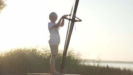 alaplap : The boy at the first windsurfing training. Introductory training, learning the basics of surfing. Close-up of a boy and a sail at sunset