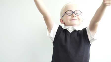 aktatáska : A boy in school uniform is happy at the first day of school. He jumps for joy, smiles and shows it cool with both hands. The boy has a school uniform and glasses. The pupil is very beautiful