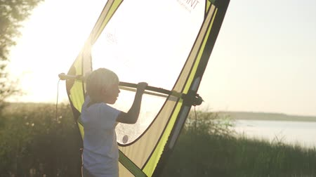 alaplap : The boy learns to windsurf. Training on land. Close-up of a boy and a sail. The student learns to catch the wind and drive the sail. Class at sunset. The first training. Pleshcheeva Lake. School of Su